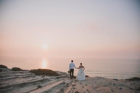 Bruidspaar op rots met uitzicht op zee
